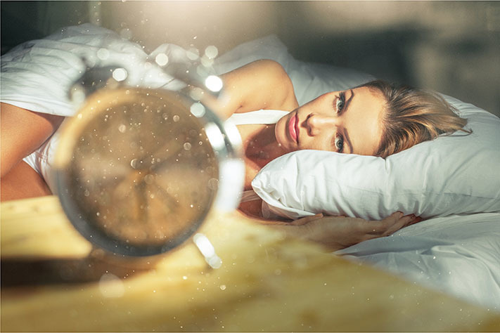 Woman laying in bed dealing with insomnia