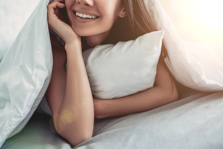 Woman smiling and holding a pillow under a weighted blanket